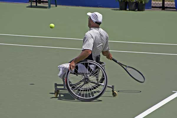 disabled man playing tennis in a wheelchair