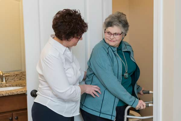 Lady with walker being assisted to the bathroom by Julie