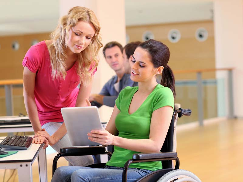 cheerful handicapped woman at work in wheelchair with coworkers